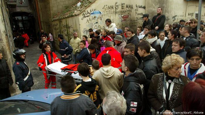 Eine Menschenmenge versammelt sich um den Schauplatz eines Verbrechens