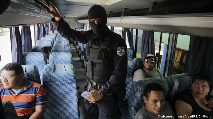 Salvadoran police check passengers on a bus