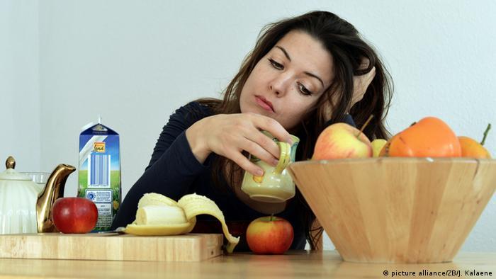 Junge Frau sitzt müde beim Frühstück (picture alliance/ZB/J. Kalaene)