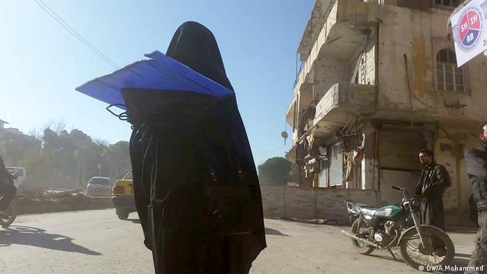 A woman in a black niqab