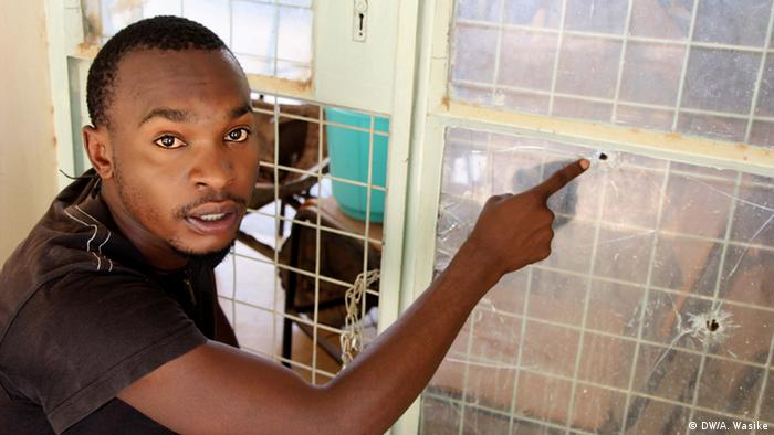 A young man points to a bullet hole in a lecture hall window pane (photo: DW/A. Wasike)