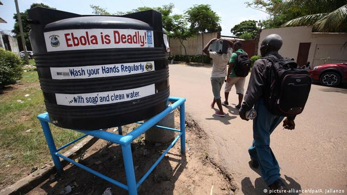 A man walks past a water tank that warns 'Ebola is deadly' (picture-alliance/dpa/A. Jallanzo)