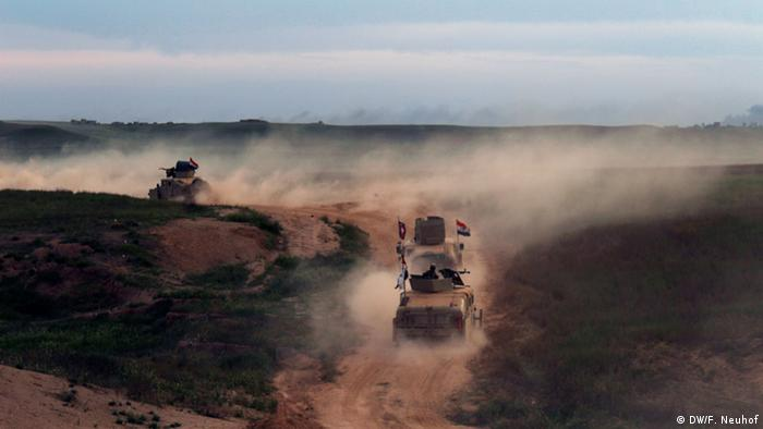 Iraqi army Humvees roll towards Nasr village at dusk