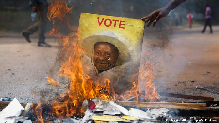 A burning campaign poster of Yoweri Museveni from 2016