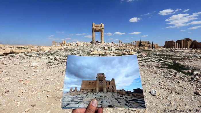 Ein Mensch hält eine Fotoaufnahme von vor der Zerstörung vor die aktuelle Sicht auf den Baal-Tempel (Foto: Getty Images)