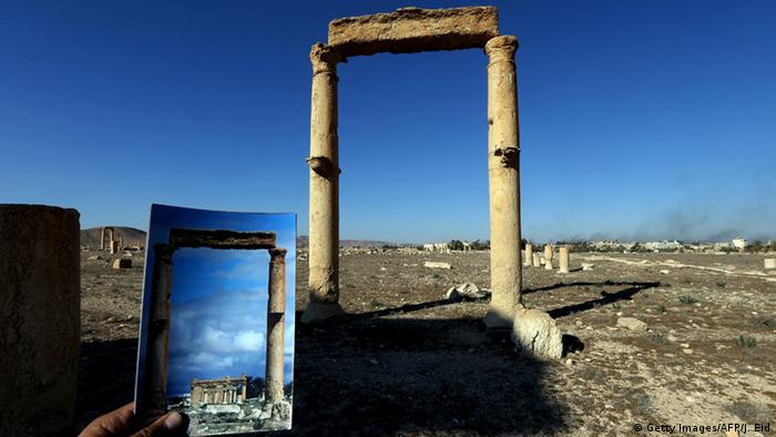 A picture taken on March 31, 2016 shows a photographer holding his picture of the Temple of Baal Shamin seen through two Corinthian columns (Getty Images/AFP/J. Eid)