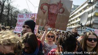 A protester holds a banner during a protest against plans of introduction of new abortion ban law in front of the Sejm (lower house of Parliament), in Warsaw, Poland, 03 April