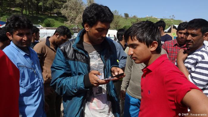 Picture of refugees in Tsamakia looking at cell phones