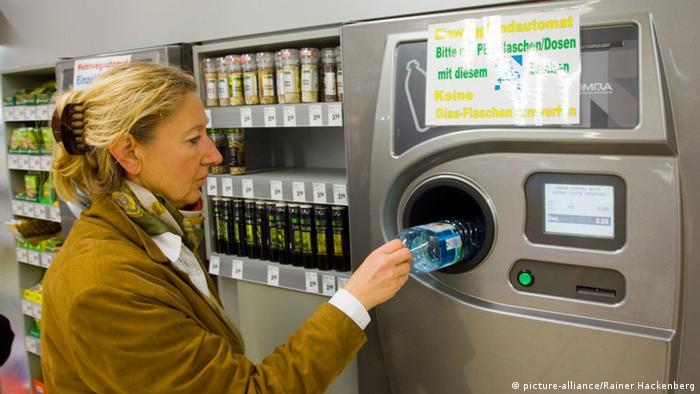 Woman returning plastic bottle at deposit machine in German supermarket (picture-alliance/Rainer Hackenberg)
