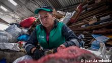 A woman sorts through recyclable materials