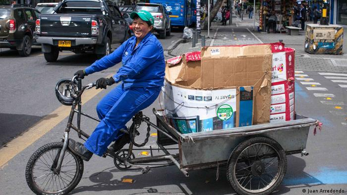 A woman cycling a cart full of recyclable materials