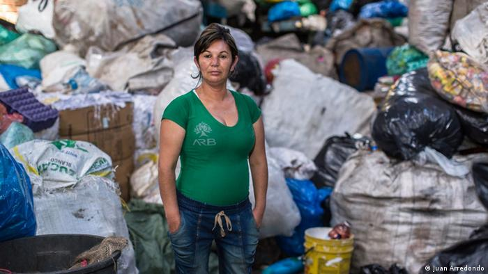 A woman in front of a pile of recyclable material