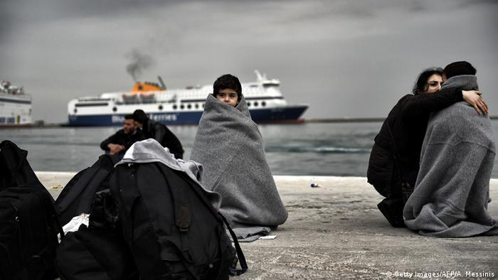 Children wrapped in covers stand in a harbour as migrants and refugees arrive on the Greek island of Lesbos