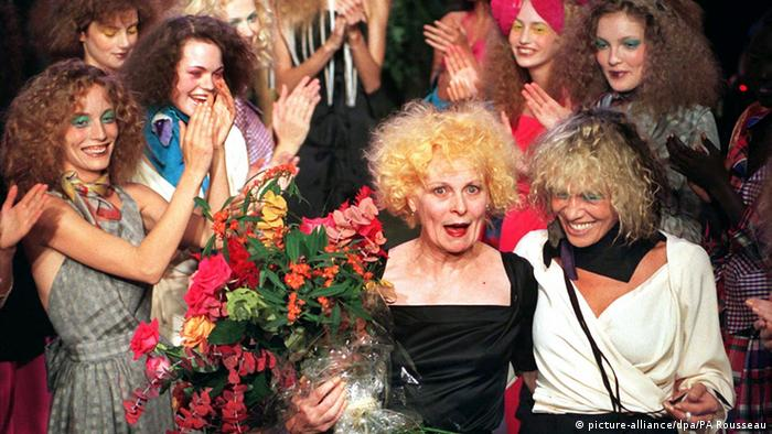 Westwood at a fashion show holding a bouquet and surrounded by models