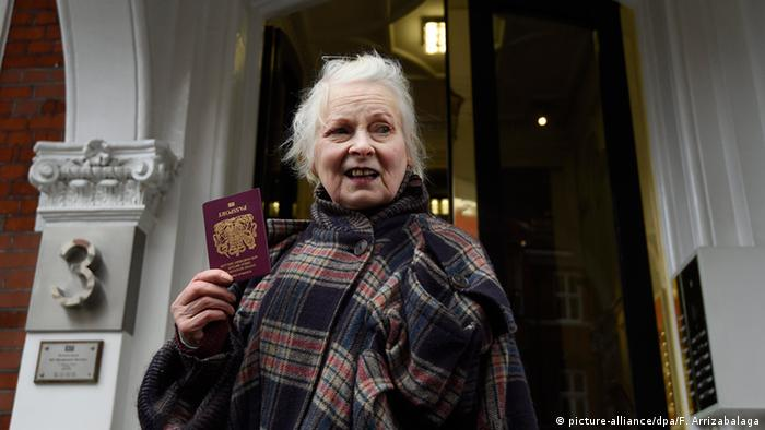 Westwood stands with her passport in front of the Embassy of Ecuador in London