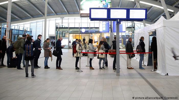 Commuters stand in line in front of a voting tent set up at the Central Station in Utrecht