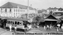 English: Steamtram in Batavia before the iron-works factory of Carl Schlieper Nederlands: Negatief. Waar stoomtreinen rijden, zijn ook stoomtrams mogelijk. Batavia kende al sedert 1869 een paardentram, maar het duurde tot 1883 voor de stoomtram kwam. De daarop volgende stap werd genomen in 1899 met de komst van de elektrische tram. In dezelfde tijd werden ook tramlijnen aangelegd in de twee andere grote steden langs Java's noordkust, Semarang en Soerabaja. Het verschil tussen stoomtram en stoomtrein was niet altijd groot. Stoomtrams hadden ook een bovenstedelijke betekenis, zoals blijkt uit de verbinding tussen Semarang en Cheribon en die tussen Semarang en Joana. (P. Boomgaard, 2001). Stoomtram in Batavia bij het gebouw van de ijzerwarenfabriek van Carl Schlieper Datum 1915-1920 (c) Collection Nationaal Museum van Wereldculturen Quelle: https://commons.wikimedia.org/wiki/File:COLLECTIE_TROPENMUSEUM_Stoomtram_in_Batavia_bij_het_gebouw_van_de_ijzerwarenfabriek_van_Carl_Schlieper_TMnr_10014232.jpg?uselang=de