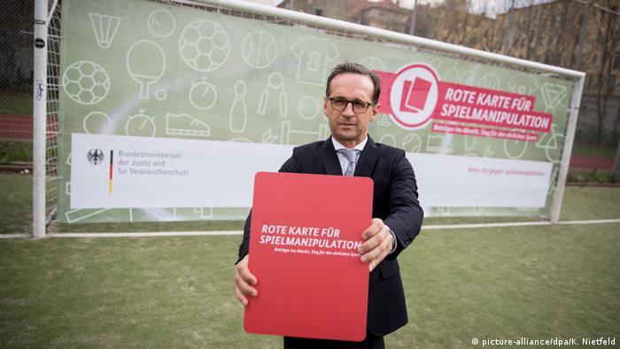 Heiko Maas mit großer Roter Karte in der Hand bei Werbetermin für Wettbetrugsgesetz (Foto: Kay Nietfeld/dpa)