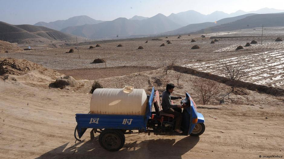 A farmer transports water through the dust bowl in China's Huining region
