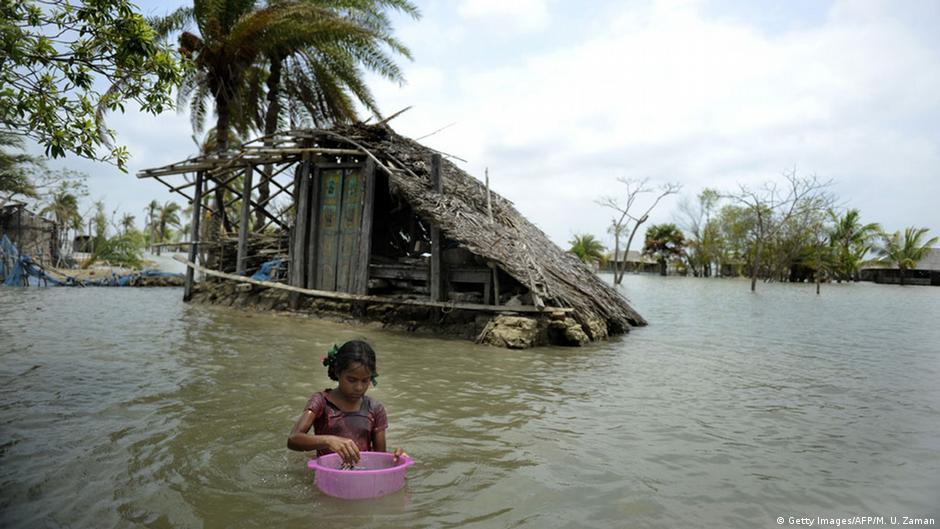A Bangladeshi child washes fish in front of a partially flooded home during tidal movements in Gabura in 2010