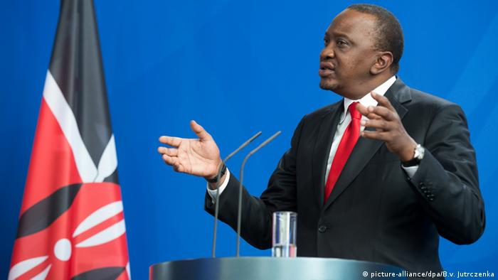 Kenya's president Uhuru Kenyatta standing in front of a blue wall with the Kenyan flag in the background.