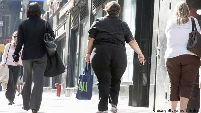Personas con sobrepeso caminando por la calle.