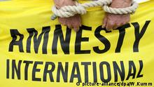 Symbolbild Amnesty International Logo Folter Todesstrafe Menschenrechte Aktivisten von Amnesty International protestieren am 28.07.2013 anlässlich der Wahlen in Mali auf dem Potsdamer Platz in Berlin. Amnesty will auf die alarmierende Menschenrechtslage und insbesondere die Häufung von Hinrichtungen in dem westafrikanischen Land aufmerksam machen. Foto: Wolfgang Kumm/dpa picture-alliance/dpa/W.Kumm