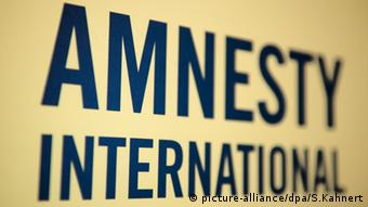 The words Amnesty International against a yellow background
