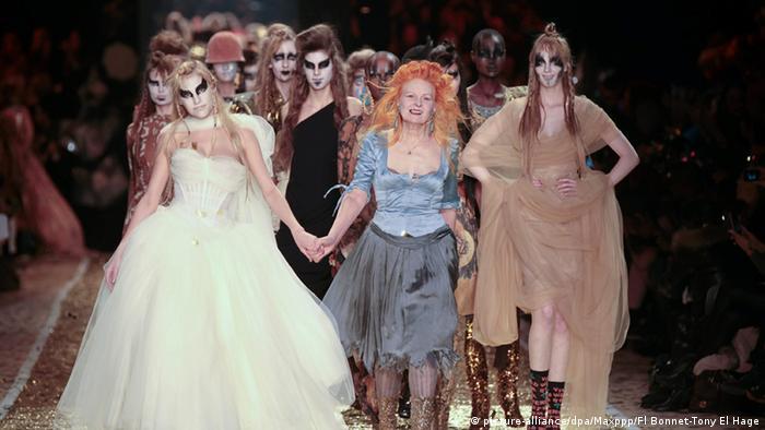 Vivienne Westwood bei der Fashionweek im März 2011 in Paris. Auf dem Laufsteg zwischen zwei Models in langen Roben.
