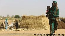 A Sudanese woman carries a baby at the Zam Zam camp for Internally Displaced People (IDP), North Darfur, on April 9, 2015. Sudan heads to the polls next week in elections widely expected to extend President Omar al-Bashir's quarter-century rule, despite his indictment for alleged war crimes, continued unrest and a faltering economy. +++ (C) Getty Images/AFP/A. Shazly