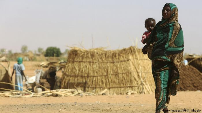 Sudanese woman carries baby in refugee camp in North Darfur (C) Getty Images/AFP/A. Shazly