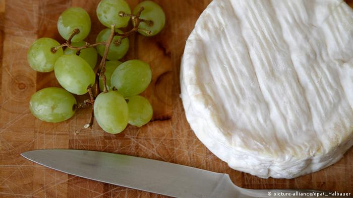 A bunch of grapes next to a wheel of brie cheese