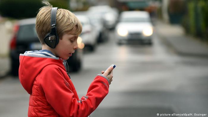 Menino com fone de ouvido e celular atravessando a rua