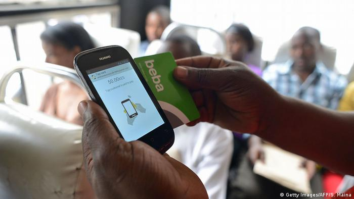 A Kenyan passenger uses on June 25, 2014 a mobile phone and a 'BebaPay' card, a mobile phone-based money transfer service that allows transit passengers to pay their bus fare without having to use cash