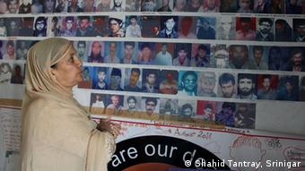 Parveena Ahangar stands in front of photos of the disappeared at the office of the Association of Parents of Disappeared People -