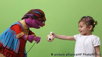 Sesame Street's new Afghan character, Zari, interacts with a little girl