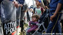 A child looks at Greek policeman after migrants and refugees tried to open the border fence at a makeshift camp at the Greek-Macedonian border near the village of Idomeni