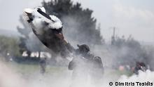 10.4.2016 *** A refugee tries to extinguish a teargas canister. Copyright: Dimitris Tosidis