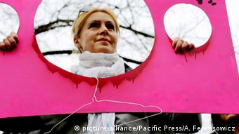 A woman holds a coat hanger, a symbol of underground abortions during a demonstration against a potential ban on abortion in Warsaw, Poland