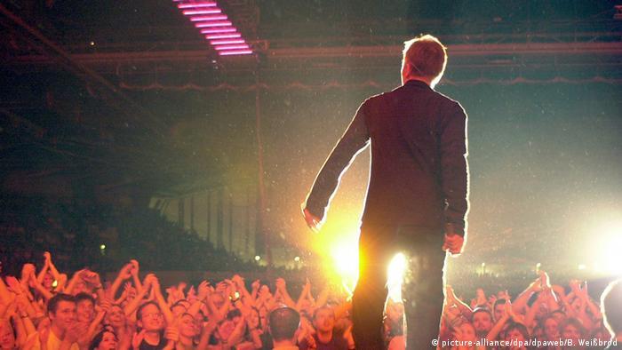 Rückansicht Grönemeyer, der, angestrahlt von Scheinwerfern, vor seinem Publikum steht. (Foto: dpa)