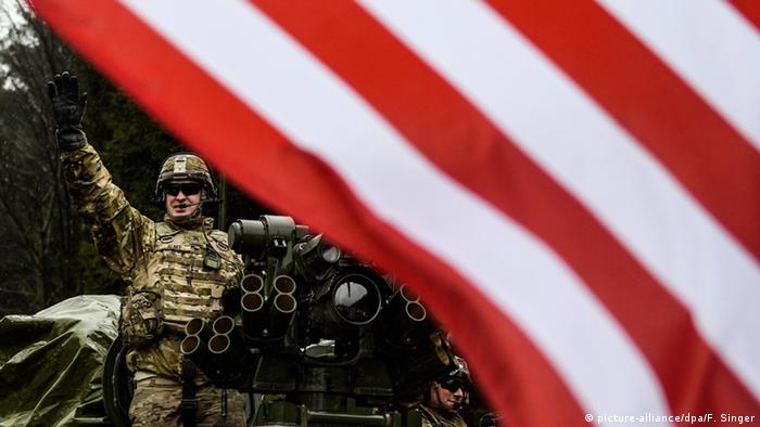 A US soldier stands on Stryker vehicle and waves as his convoy crosses into the Czech Republic in Harrachov