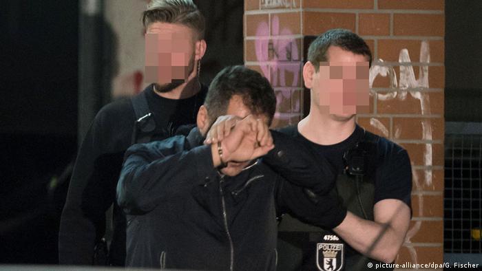 Задержанный закрывает лицо руками перед камерой, за ним - двое полицейских