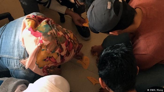 Five young people sit on the floor in order to write words on cards.