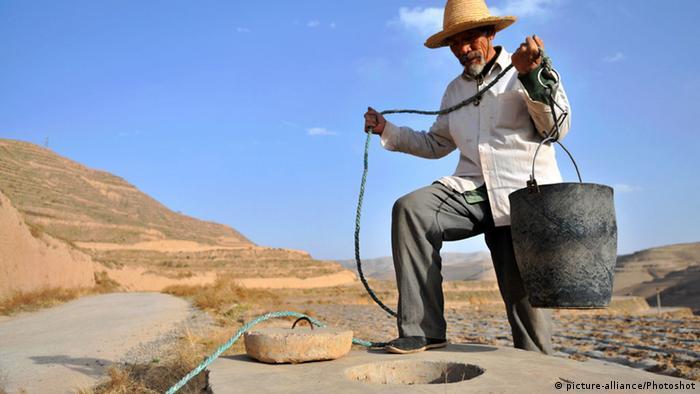 China Bauer holt Wasser an einem Brunnen