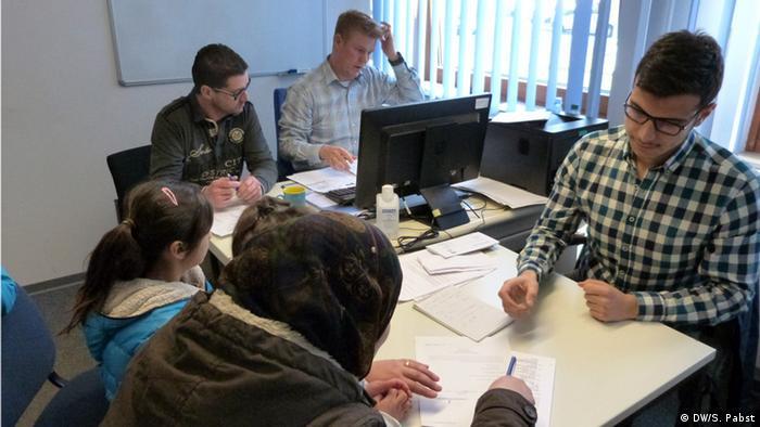 Bir aile, iltica başvurusu belgelerini Federal Göç ve Mülteci Dairesi'ne (BAMF) iletiyor