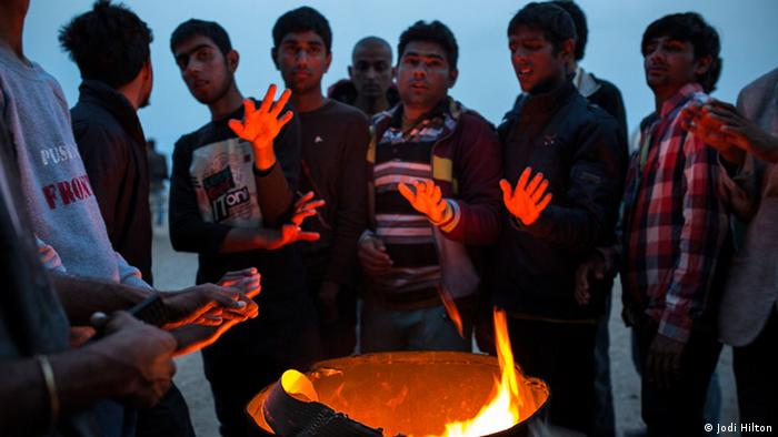 Pakistani men warm themselves by a fire