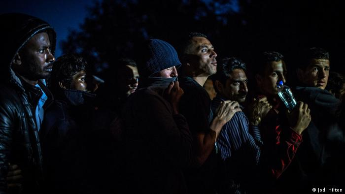 Men wait in line in the dark to get food