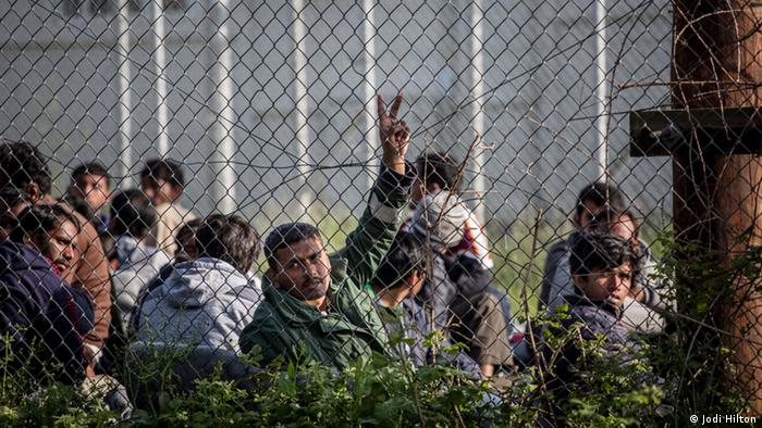 A man makes a peace sign as he sits with others behind a fence at Moria Camp
