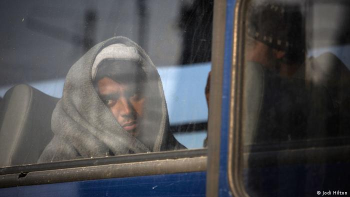 A young man wrapped in a blanket looks out a bus window