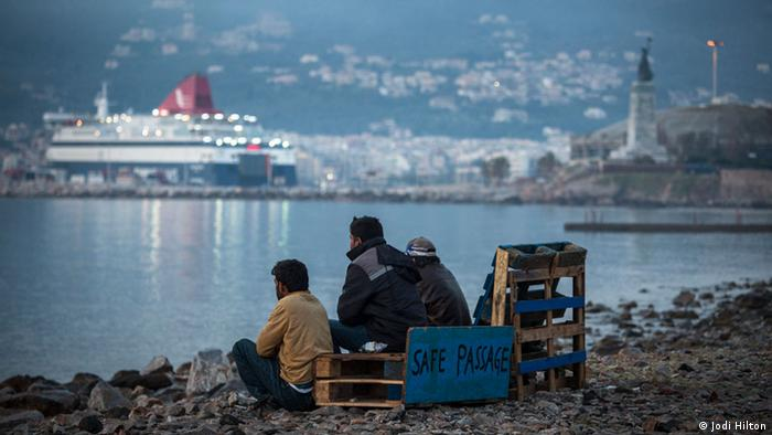 Pakistani migrants sit on a Lesbos beach next to a sign reading Safe passage and looking out at the water